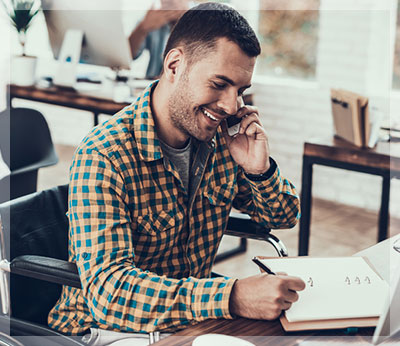 man smiling and talking on the phone while taking notes
